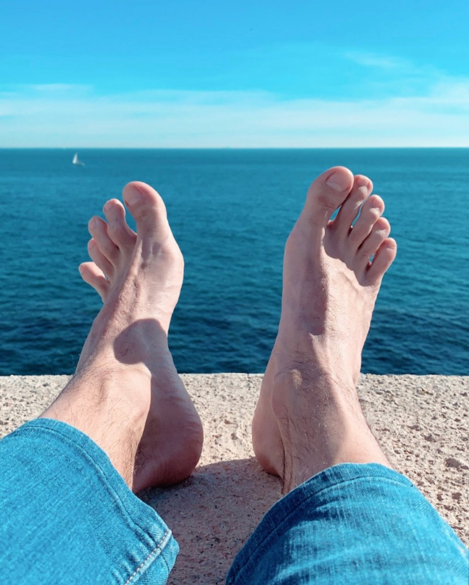 Ilopexfeet's bare feet in blue jeans by the water