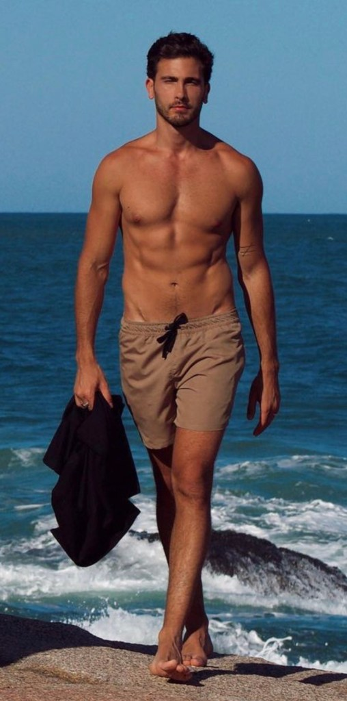 jbossle shirtless and barefoot walking out of the water
