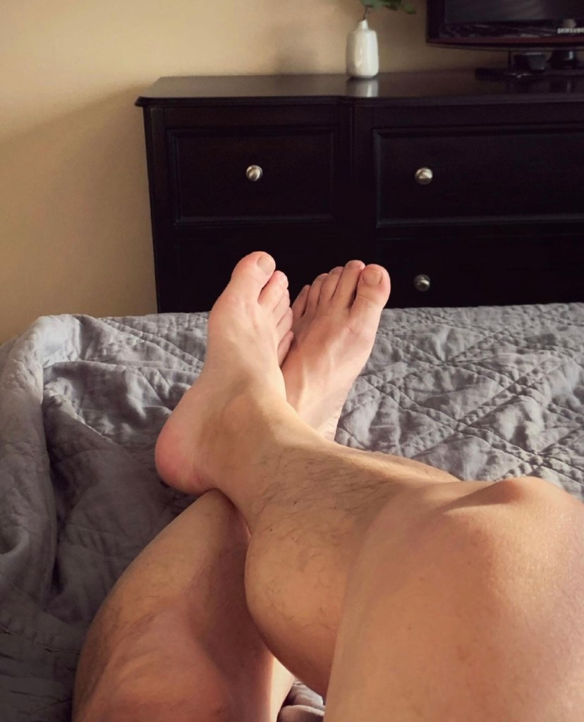 Bro.toes' bare legs and feet tops on the bed