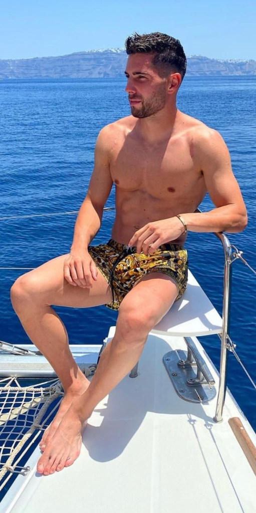 Bearded and shirtless Luca Zidane barefoot on a boat
