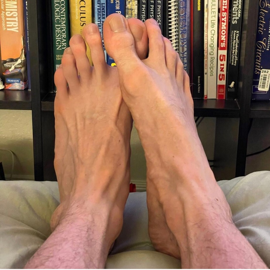 thatmidwestfootguy's size 10.5 bare feet by the bookshelf
