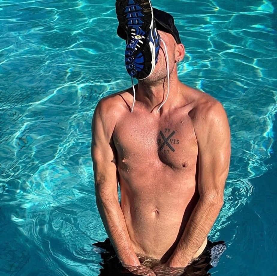 Sockssportkinky shirtless and sniffing his Nike sneaker in the pool