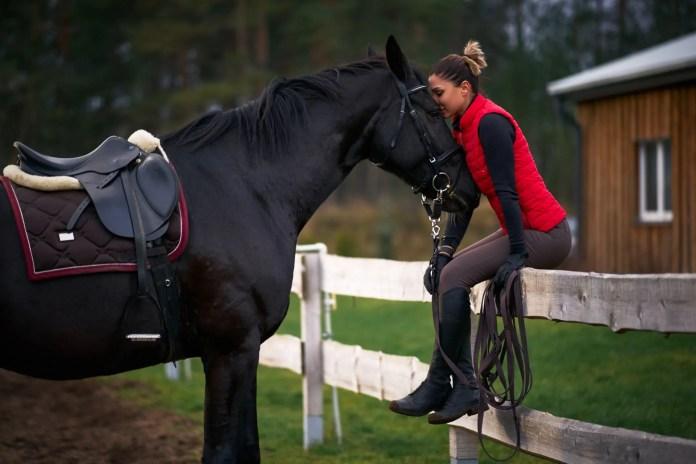 Kvinde sidder på ridebanehegn med hest i hånden.