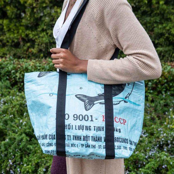 woman carrying light blue beach bag