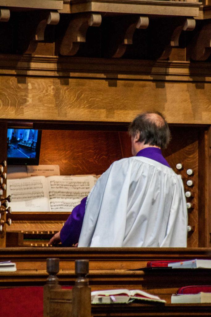 Organist and choir master John Hughes playing the Abbey organ