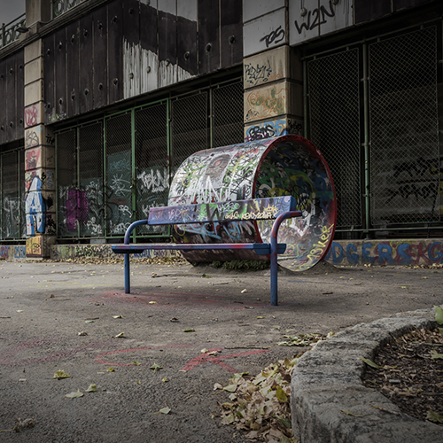 street bench with graffity tags