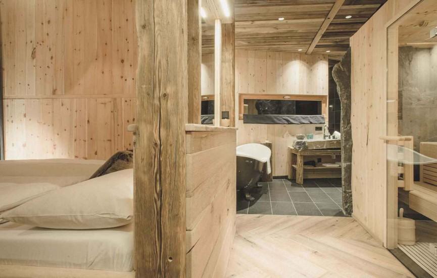 Hotelzimmer woodenstyle & spa. Freistehende Badewanne mit einem Traumblick auf die Pinzgauer Berge und private kleine Sauna zum Entspannen.