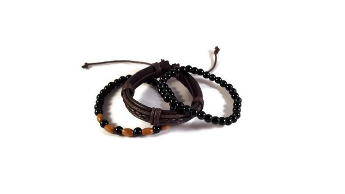 MamaBella AM0005 Dublin armbandenset is een set elastische herenarmbanden bestaande uit een armband van zwarte glaskralen, een donkerbruine gevlochten lederen armband en een armband van zwarte glaskralen en ovale lichtbruine houten parels