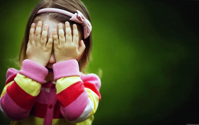 menina escondendo o rosto