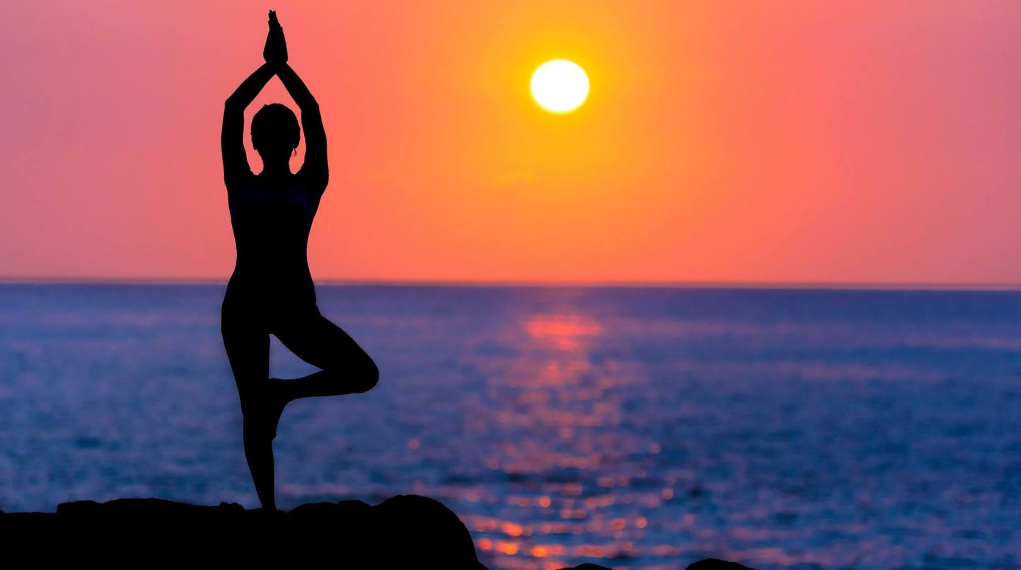 Silhouette of woman doing yoga on background of red sky and blue water