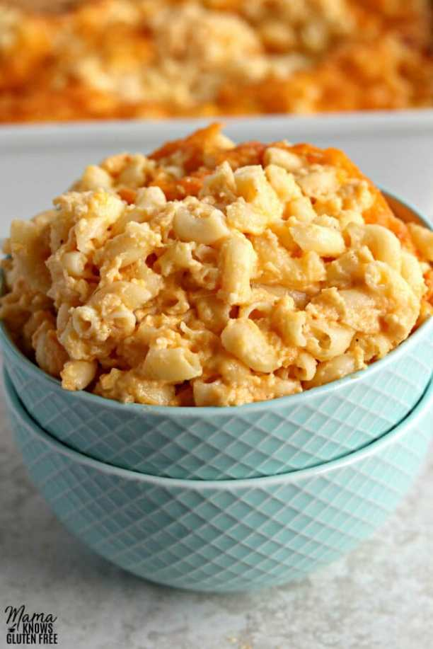gluten-free macaroni and cheese in a blue bowl with a casserole dish in the background