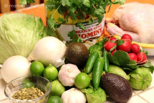 Una lata de maíz pozolero, y otros ingredientes para hacer pozole verde de pollo como cebolla, tomates, chiles.