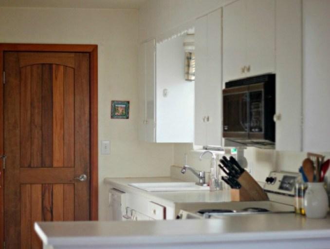 Cocina de color blanco con una puerta de madera al fondo