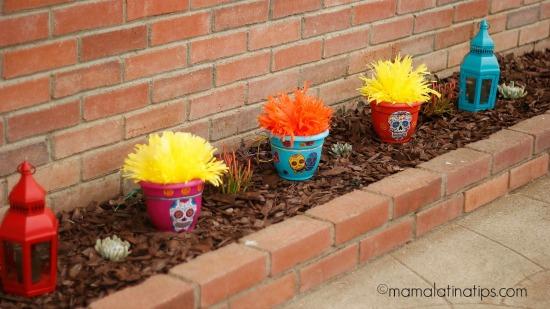 Macetas coloridas adornadas con calaveras y flores de papel