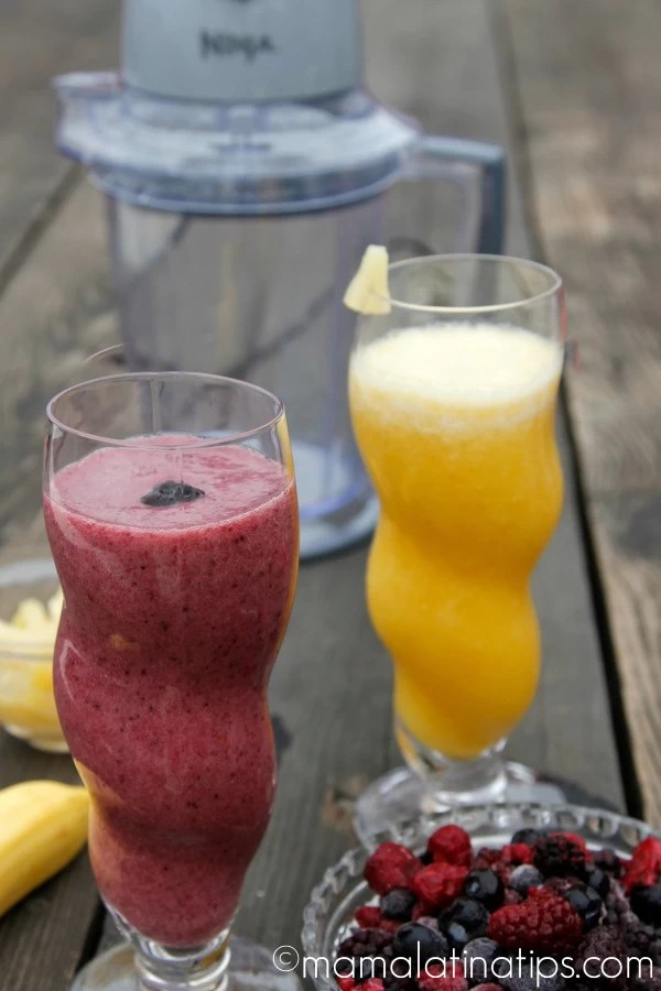 berry smoothie and pineapple smoothie on a wooden table