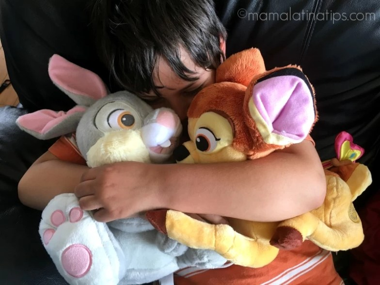 Kid hugging Bambi and Thumper plush toys - mamalatinatips.com