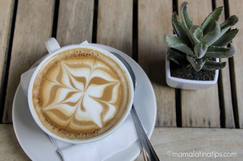 Taza de café con leche con un diseño floral en la espuma