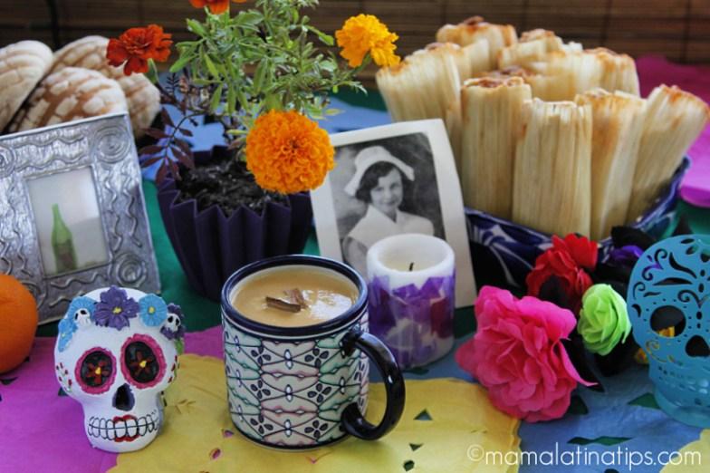 Una mesa con ofrenda de día de muertos, tamales, flores, pan dulce y una taza con atole.
