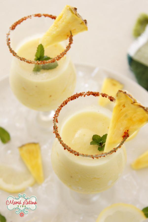Margarita de piña congelada en un vaso con una ramita de menta