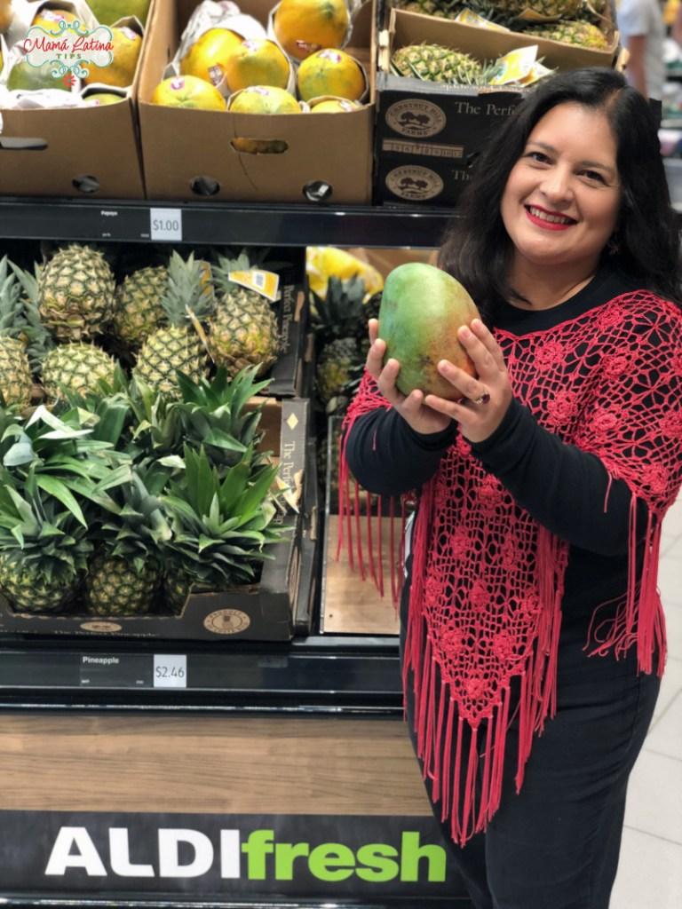Mujer con un mango en sus manos en un supermercado