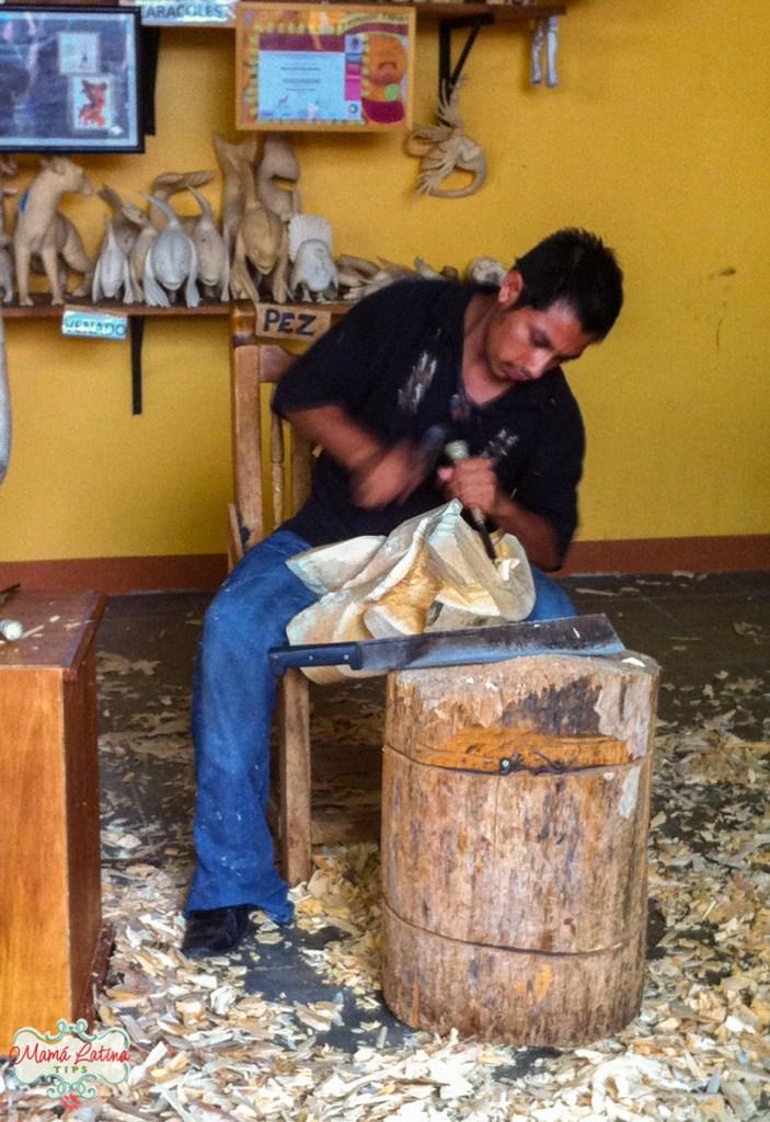 Artista esculpiendo un alebrije de madera de copal