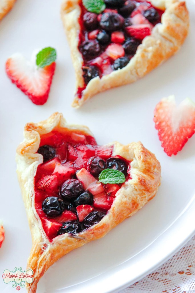 Two fruit tarts on top of a white plate and heart shaped strawberries around