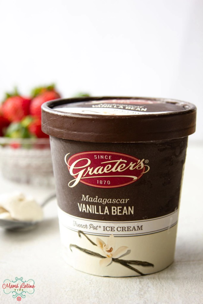 A pot of Graeter's Madagascar Vanilla Bean ice cream in front of a plate with strawberries
