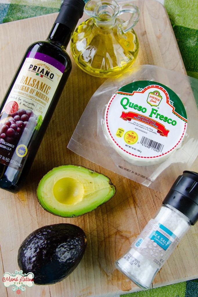 vinagre balsámico, aceite de oliva, un paquete de queso fresco, aguacate y sal sobre una tabla de madera