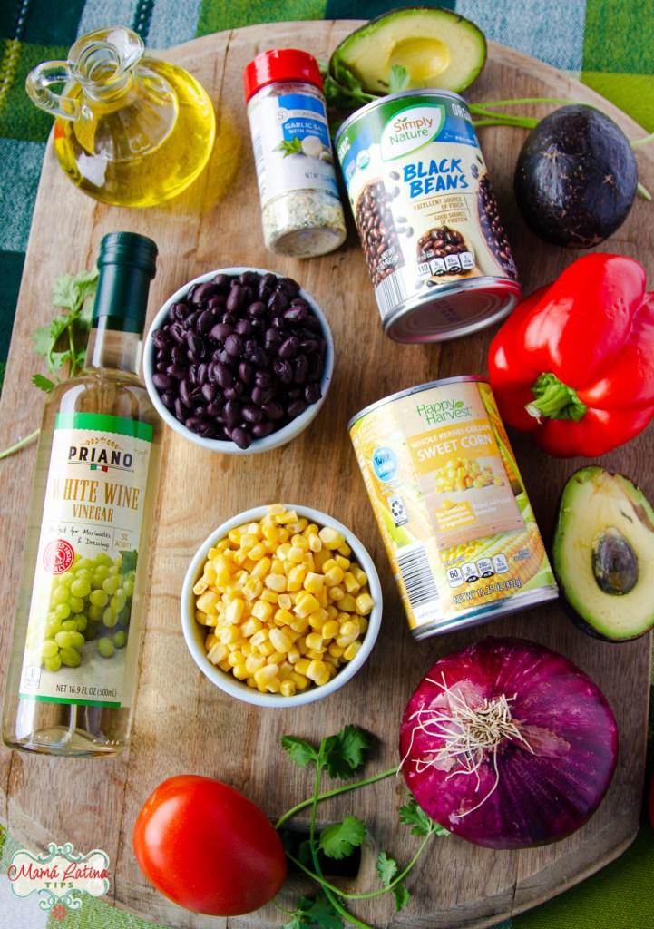 Varios ingredientes como frijoles negros, elote, latas de verduras, vinagre y aguacate sobre una tabla de madera.