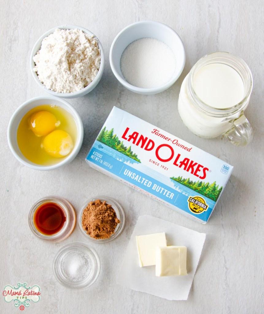 harina, azúcar, leche, huevos, vainilla, sal, cocoa, y una caja de mantequilla Land o Lakes