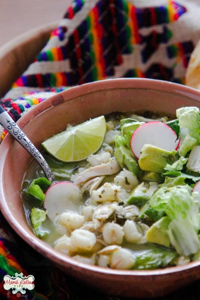 Plato café con pozole verde con pollo, verduras y una rebanada de limón
