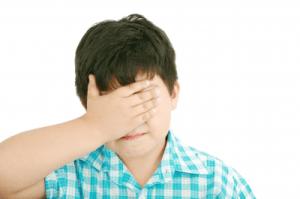 niño triste tapándose la cara