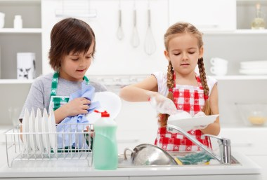 Kids washing the dishes in the kitchen together - helping out wi
