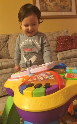 baby playing with music activity center