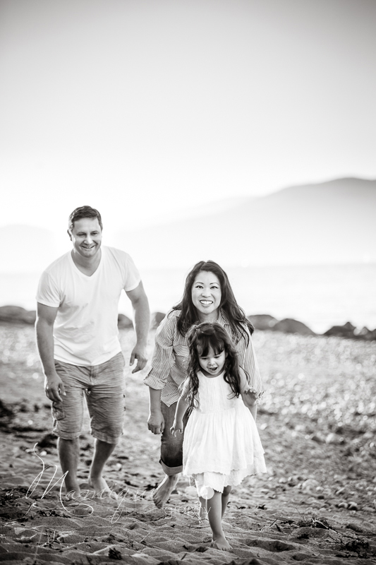 Family running on the beach in Vancouver