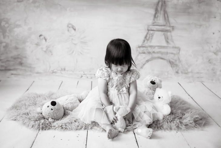 toddler girl surrounded by teddy bears