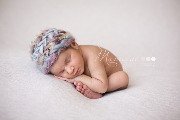 newborn girl in womb pose wearing purple hat with jewels posed like a taco