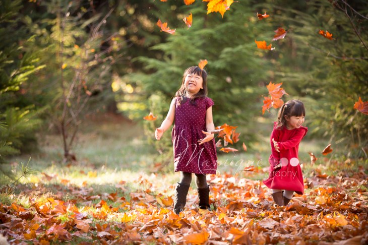 Girls having fun with fall leaves throwing on a sunny Autumn day in Vancouver