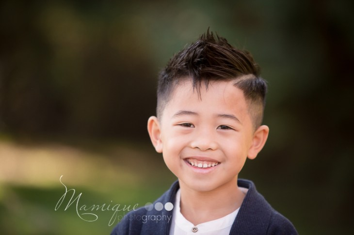 Smiling boy photograph on green outdoor background