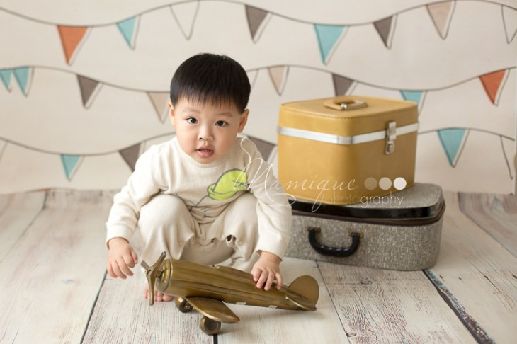 Small Boy playing with toy airplane and suitcases