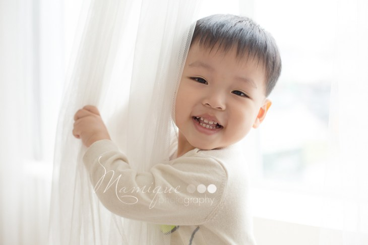 Smiling boy playing peek-a-boo by the window