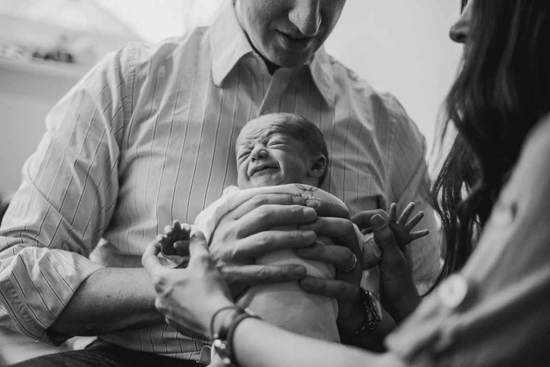 photo of a dad holding a crying newborn baby