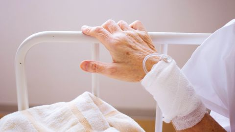 main-d-un-patient-sur-un-lit-d-hopital-avec-intraveineuse_6136344