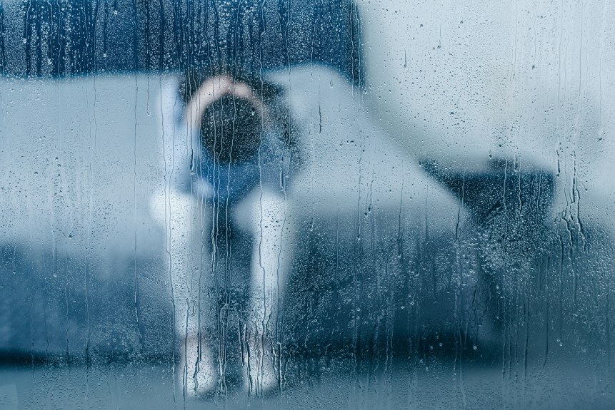Depressed woman sitting on bed and holding head in hands through window with raindrops. (c) AndrewLozovyi VIA Depositphotos.com.