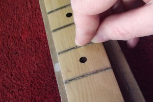 Scraping lacquer from the frets using a modified round-headed nail