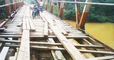 Seorang perempuan harus turun dari kenderaan melewati jembatan di titik Desa Air Apa KM 18 Sinunukan yang rusak parah