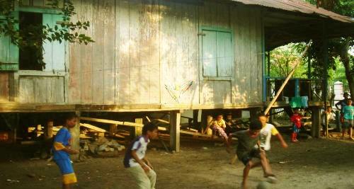 Anak-anak bermain bola di samping rumah panggung