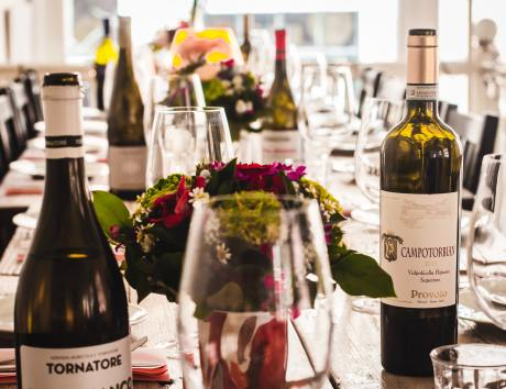 table filled with wine and glasses with flowers