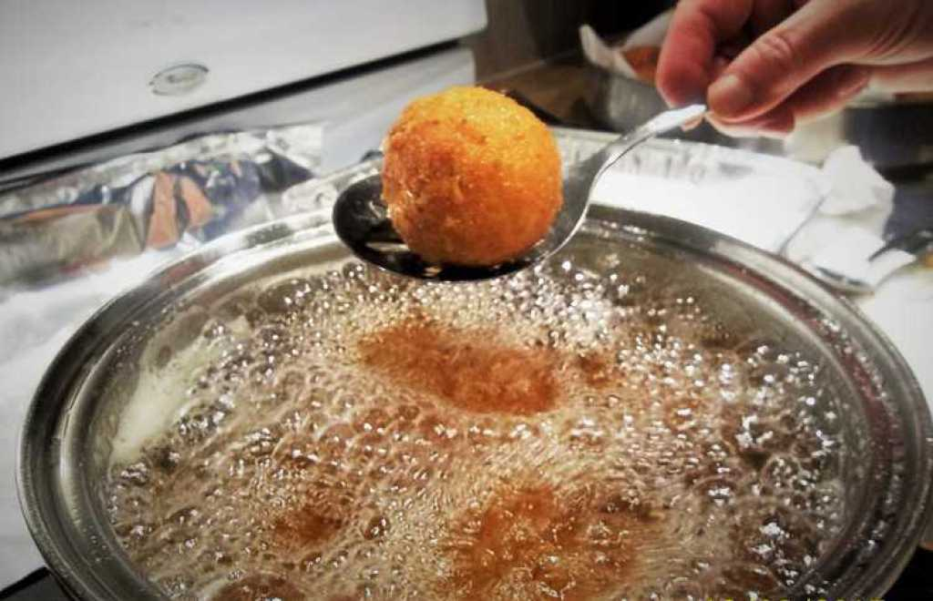 arancini being removed from a pot of oil