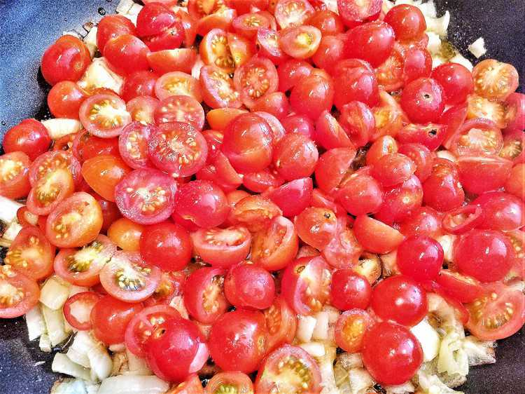 pan full of diced onions and halved cherry tomatoes